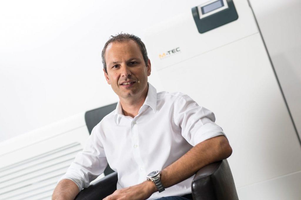 DI (FH) Peter Huemer sitzend vor einer Wärmepumpe